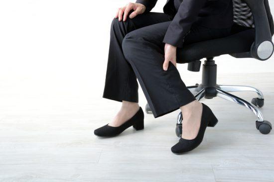 仕事中にスーツ姿でふくらはぎを揉むシーン