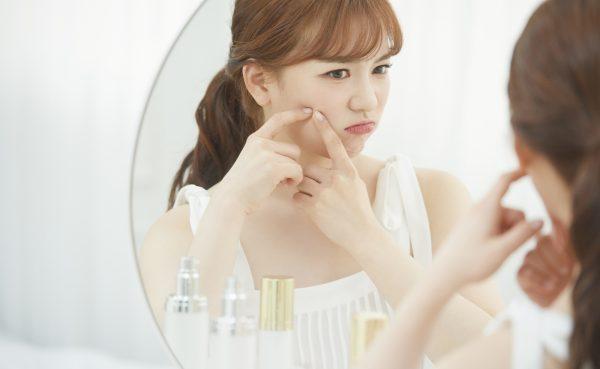 鏡越しに肌の調子を確認する女性