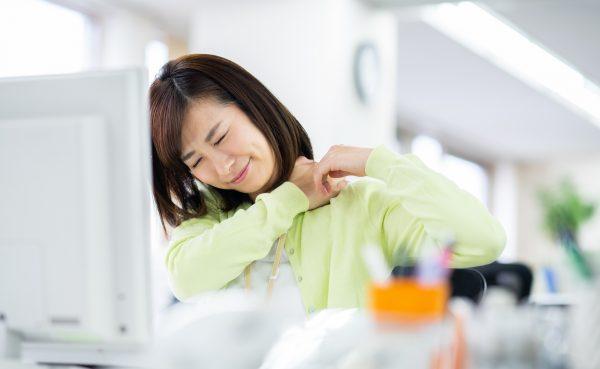 仕事中に肩を揉む女性