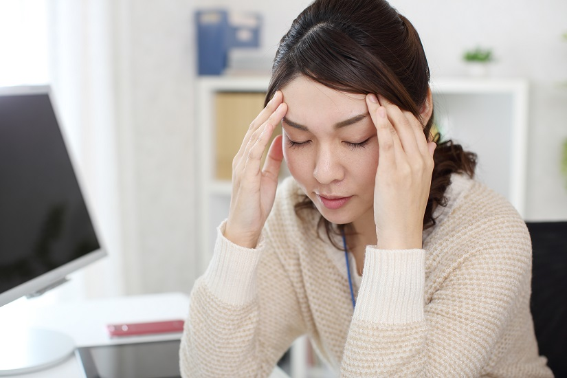 頭痛と肩こりに悩む女性