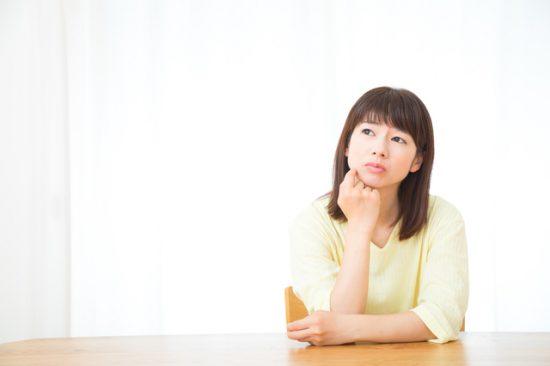 頬杖をついて悩む女性