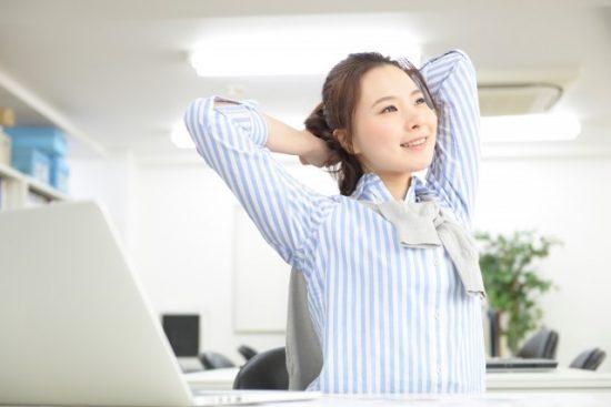 会社で伸びをする女性