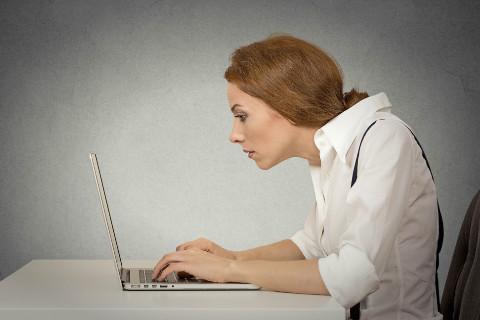 猫背&巻き肩でパソコンを操作する女性