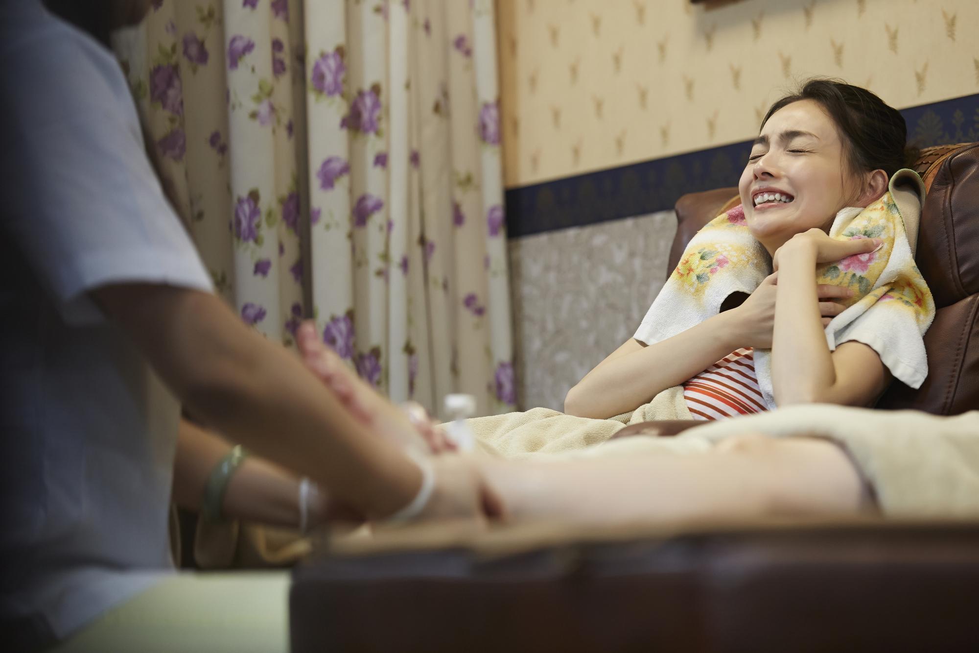 足つぼマッサージの激痛にもだえる女性