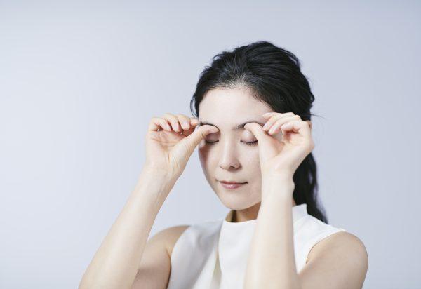 眉毛をマッサージする女性