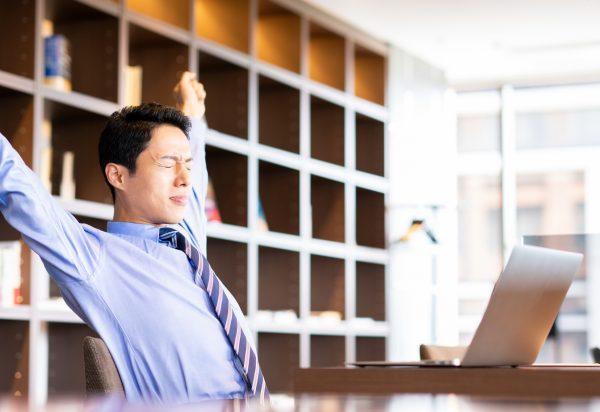 職場で背中のストレッチをする男性