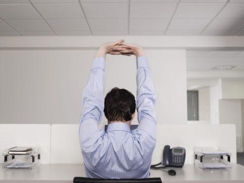 仕事中に伸びをする男性