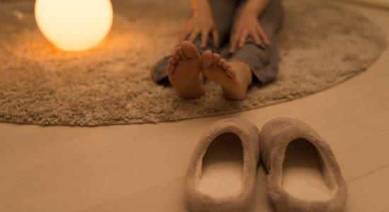 自宅で足をストレッチする女性