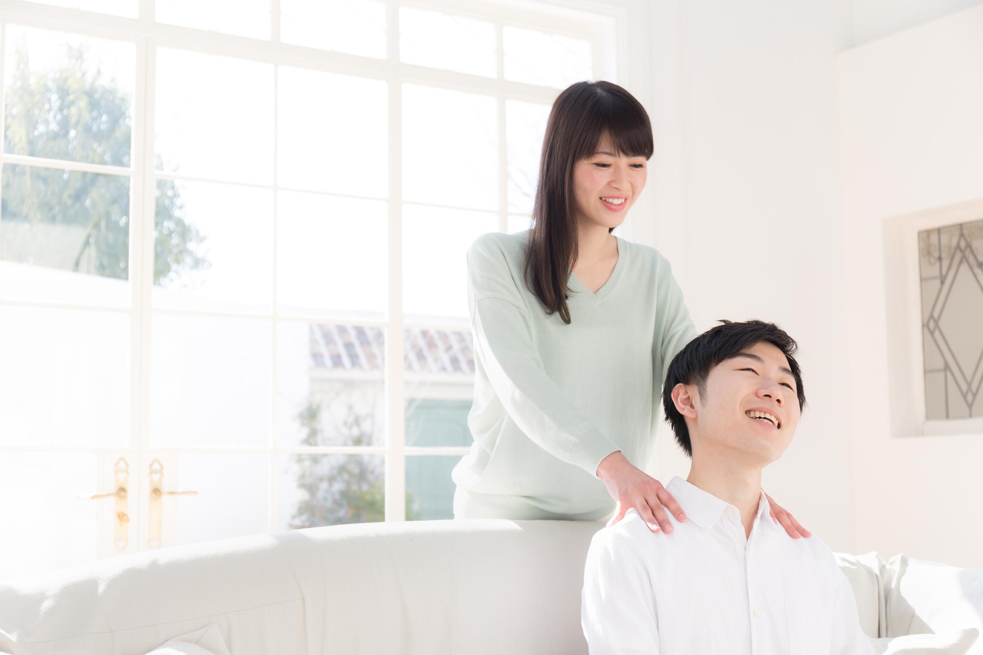 夫の肩をマッサージする女性